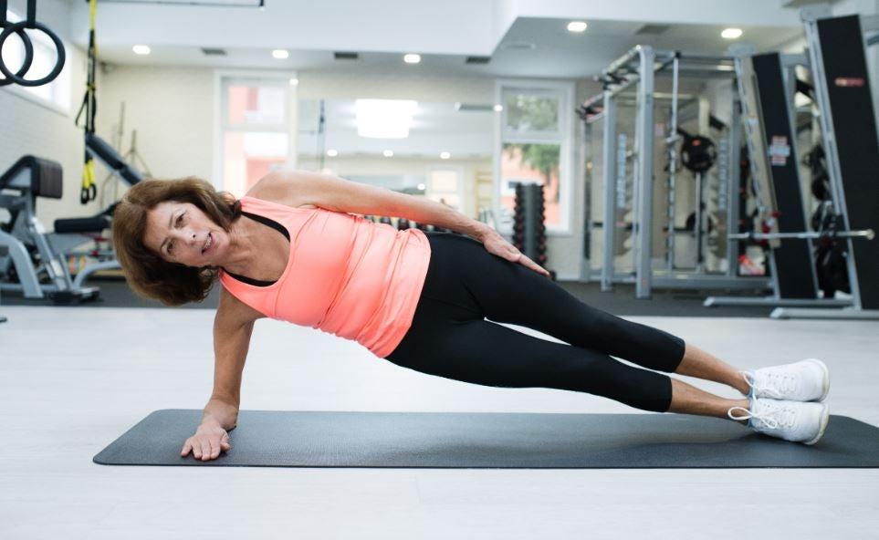 Kvinde der laver sideplanke i et fitnesscenter