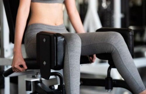 kvinde bruger maskine til træning af sine abductor-muskler