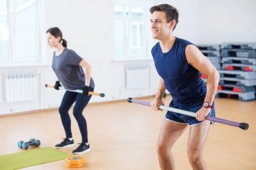 mand og kvinde træner ben med vægtstænger