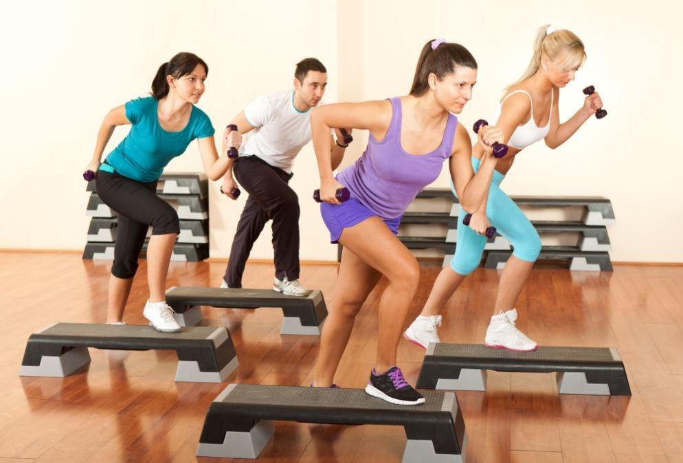 Folk der træner på et fitnesshold med vægte
