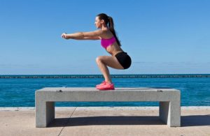 Kvinde træner calisthenics ved vandet.