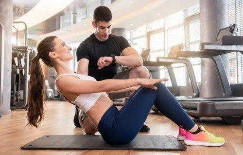 kvinde laver mavebøjninger med personlig træner