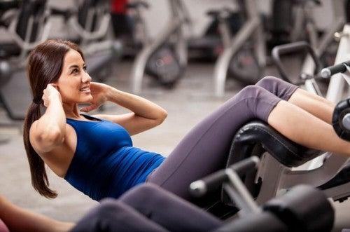 kvinde laver mavebøjninger i fitnesscenter