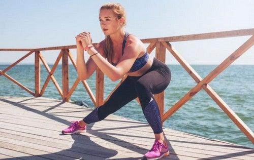 kvinde laver lateral squats ved vandet