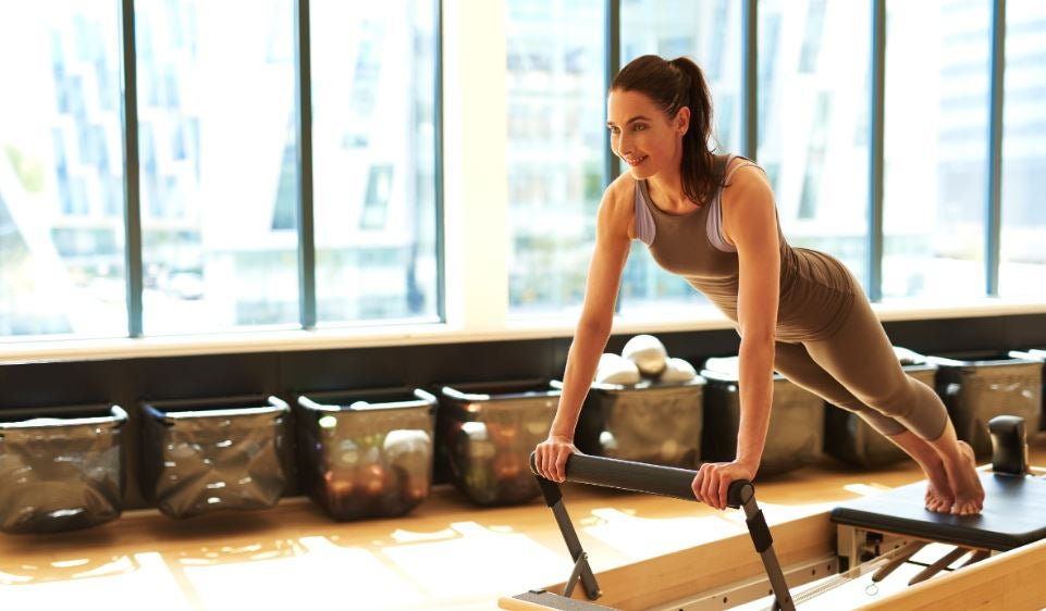 Kvinde på en maskine der kan hjælpe dig med at komme i gang med pilates