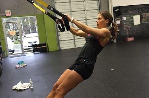 Kvinde der træner med trx i fitness