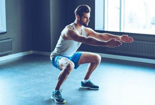 Mand der laver squats i et fitnesscenter