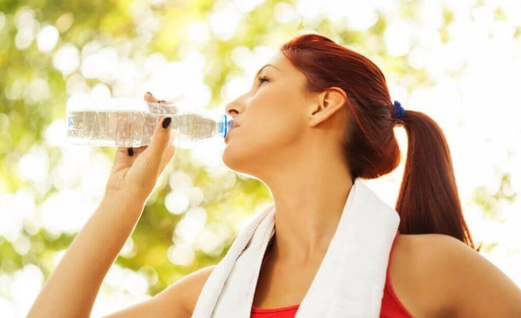 Kvinde drikker vand mens hun træner