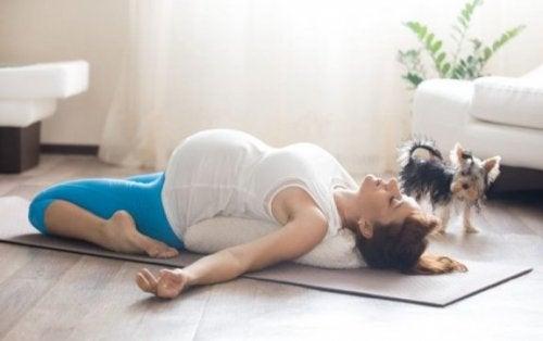 gravid kvinde der laver øvelser på en måtte