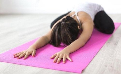 kvinde der laver yogaøvelse på en måtte