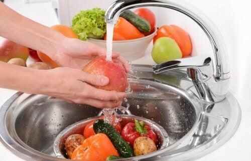 kvinde der er ved at vaske frugter og grøntsager