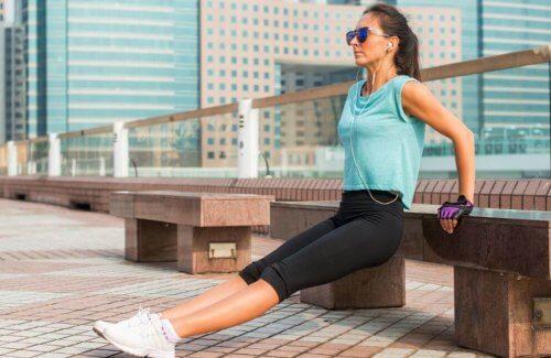 kvinde der laver træningsøvelser for begyndere udenfor på en bænk