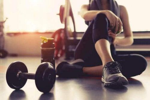kvinde strækker ud efter dumbbell upright row øvelse