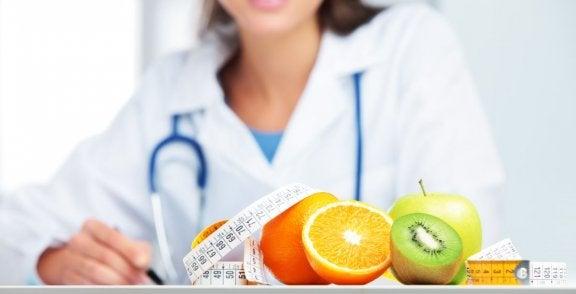 Læge sidder med målebånd og frugter