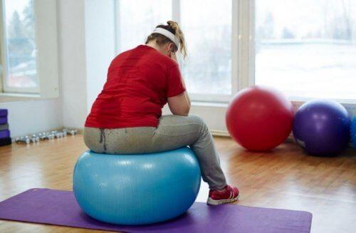 kvinde der sidder på en pilatesbold
