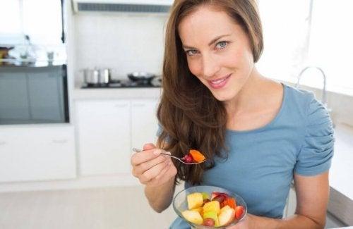 kvinde der spiser frugtsalat