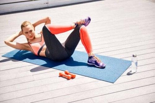 kvinde der træner mave på en måtte