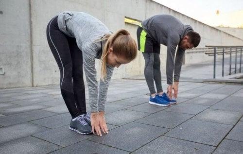 Kvinde og mand laver strækøvelser efter intens træning