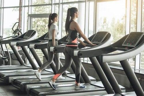 Kvinder går på løbebånd i fitnesscenteret