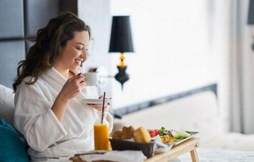 Kvinde spiser morgenmad på sengen
