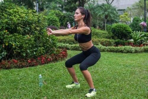 Kvinde laver squats i haven