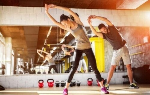 Mand og kvinde strækker ud i fitnesscenteret