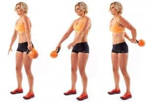 kvinde fører kettlebells rundt om kroppen