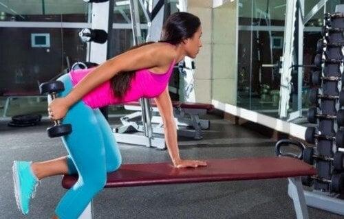 Kvinde træner med håndvægte i fitnesscenteret