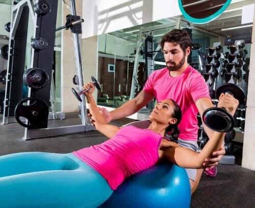 Kvinde laver brystøvelser med træner