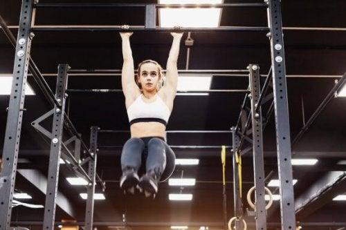 kvinde der træner i pull-up bar