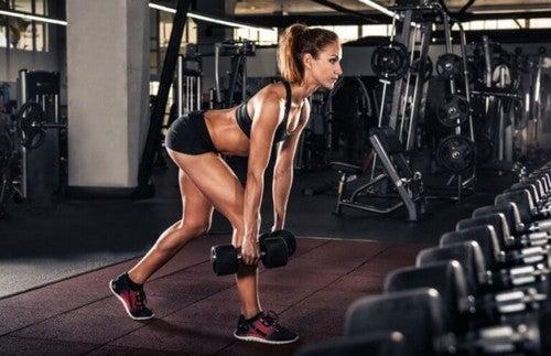 Kvinde løfter håndvægte i fitnesscenteret