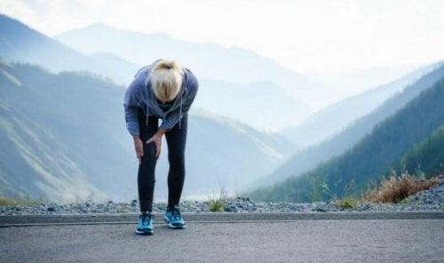 kvinde med ondt i knæet under løb