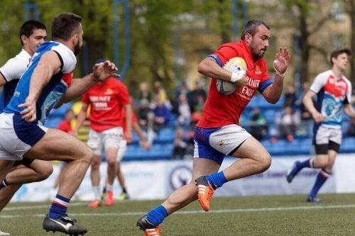Rugbyspillere løber på banen