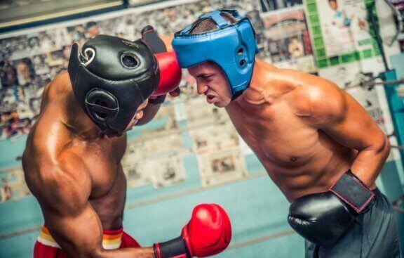 To mænd bokser med hjelme og mundbeskyttere.
