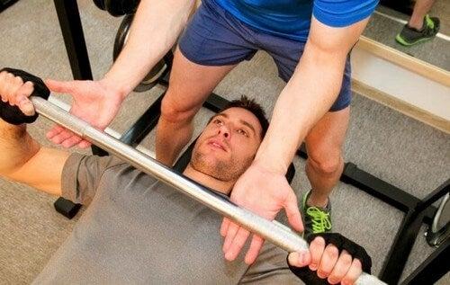 Mand får hjælp under træning