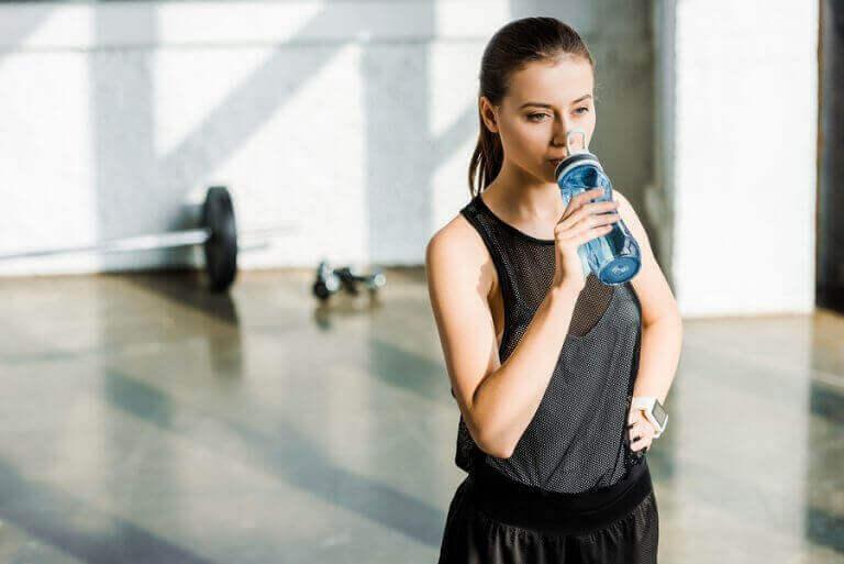kvinde der drikker af flaske
