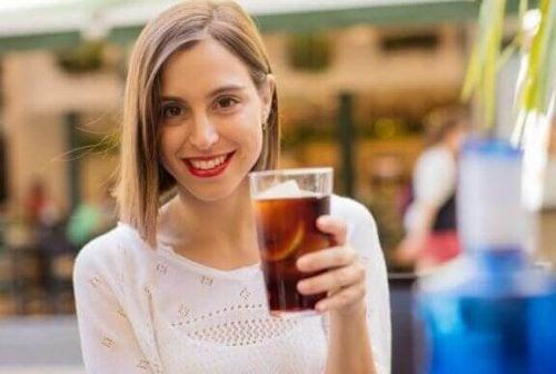 ung kvinde med et glas sodavand