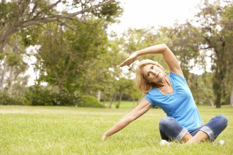 ældre kvinde der dyrker yoga udenfor