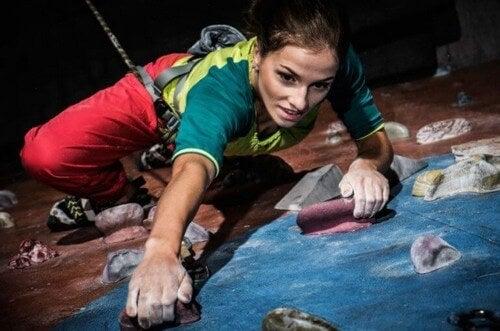 Kvinde klatrer op ad klatrevæg