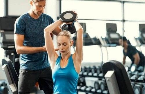 Kvinde får hjælp til vægtløftning i fitnesscenteret
