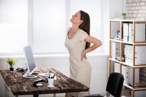 Kvinde har ondt i ryggen efter at have siddet for meget ned