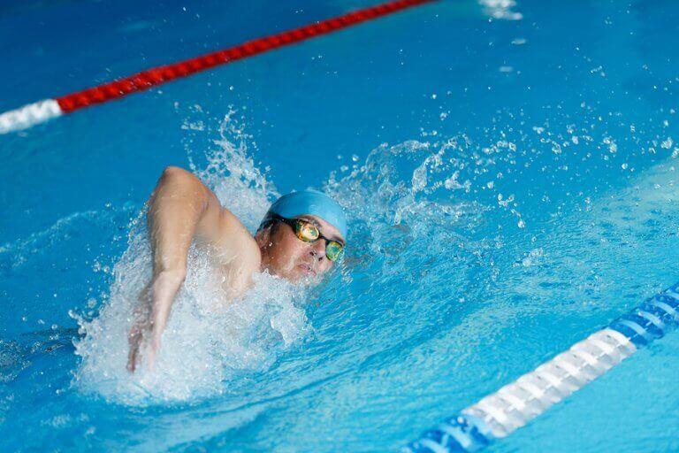 mand der svømmer på bane