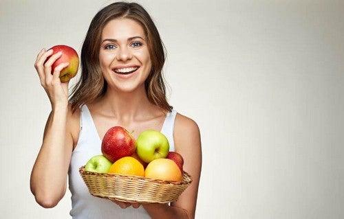 Glad kvinde holder en kurv med æbler