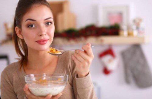 kvinde der spiser morgenmadsprodukt med mælk