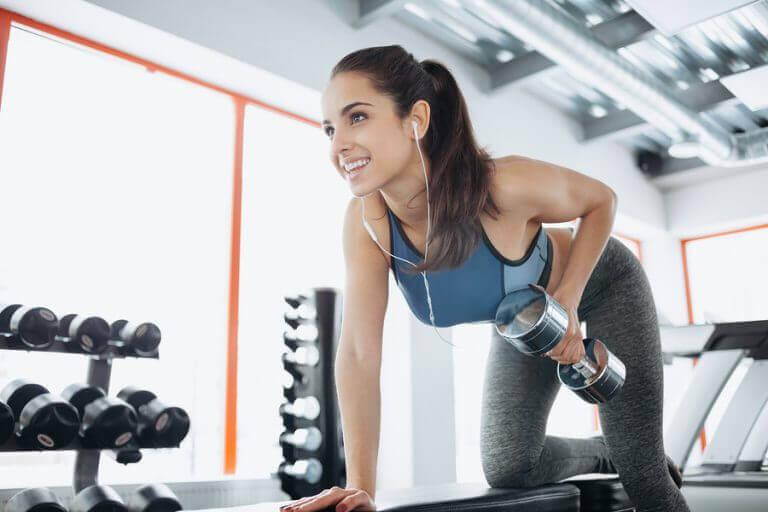 kvinde der træner ryg med håndvægt