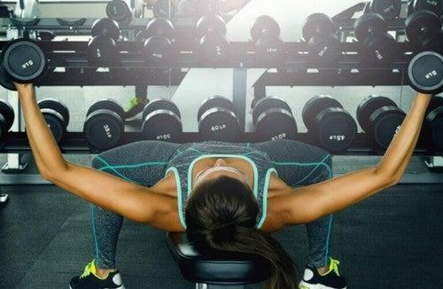 Kvinde træner med frie vægte