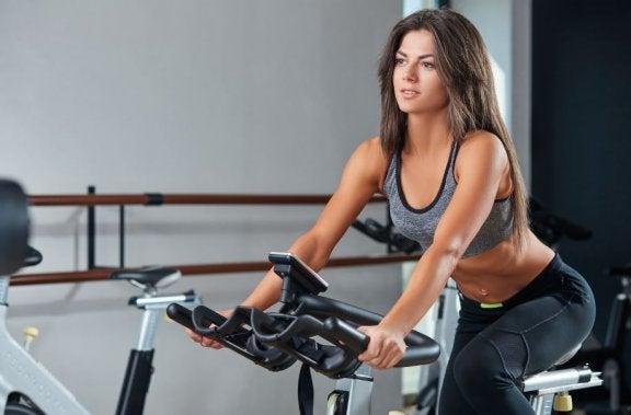 kvinde på stationær cykel