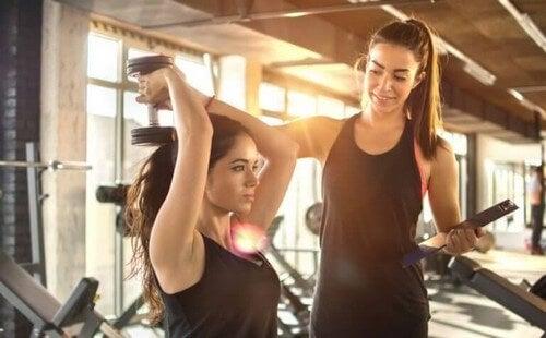 Kvinde træner med vægte med hjælp fra en personlig træner