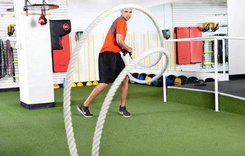 Mand træner med battle ropes i fitnesscenteret