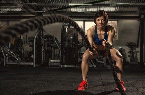 Kvinde udfører træningsøvelser med battle ropes